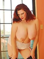 Redhead BBW shoves a hard cock between her massive tits!